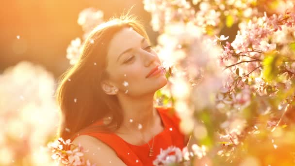 Beautiful young woman smelling a flowering branch of a tree