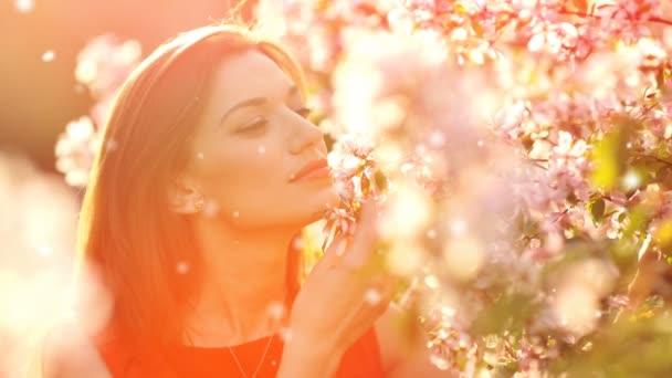 Krásná mladá žena voní kvetoucí větve stromu
