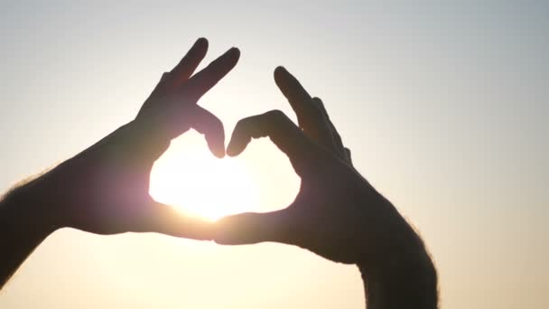 Dívka se drží za ruce ve tvaru srdce na pozadí slunce při západu slunce u moře nebo pobřeží oceánu. Žena drží symbol lásky za ruce proti západu slunce na pláži
