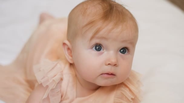 Beautiful Smiling Baby: A gorgeous little baby girl lies on white blanket and smiles at the camera with a nice big eyes. close up 4k video