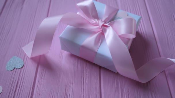 Dárková krabička se stuhou a konfetami v podobě srdce na růžovém dřevěném pozadí s místem pro text. Video na Valentýna, Den matek nebo Narozeniny. Hd horního pohledu