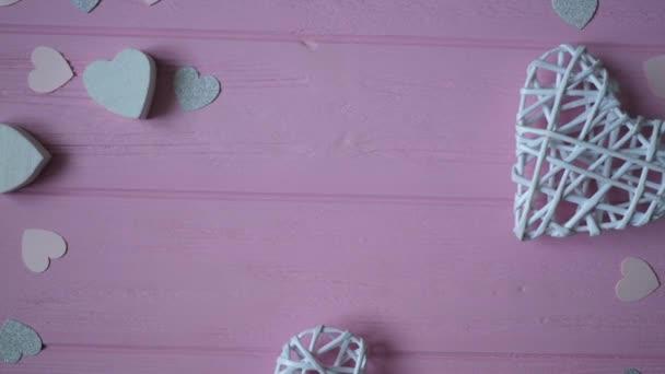 Stuha a konfety v podobě srdce na růžovém dřevěném pozadí s místem pro text. Video na Valentýna, Den matek nebo Narozeniny. Hd horního pohledu