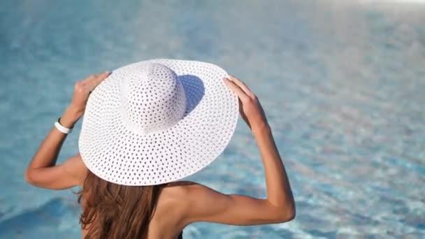 Közelkép. Homályos víz háttér. Egy fiatal nő nagy fehér kalapban ül a medence mellett, és megtartja a kalapját. Van hely az sms-nek. 4k videó Prores-ban 3840x2160