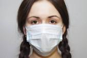Schöne junge Mädchen mit Zöpfen in einer schützenden medizinischen Maske