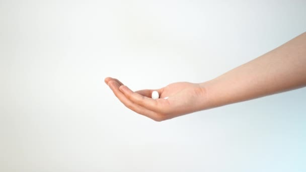 Prášky padají dívce do otevřené dlaně.