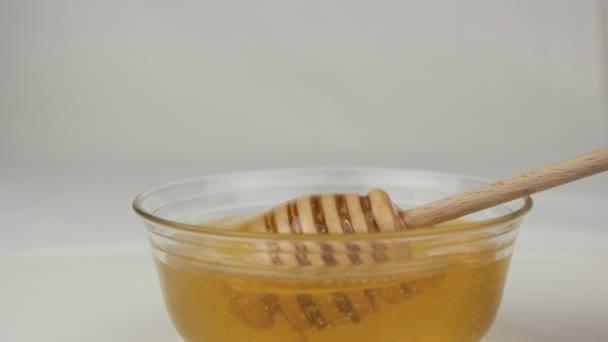 Med v skleněné mísy a dřevěné naběračky