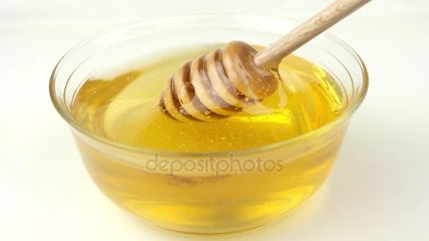 med ve skleněné míse a dřevěné naběračky