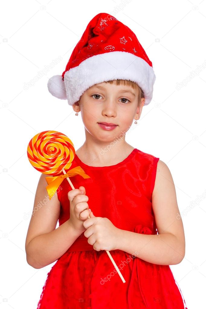 38951ecaf0662 Christmas Portrait of a beautiful little child girl wearing a santa hat and  holding a candy cane