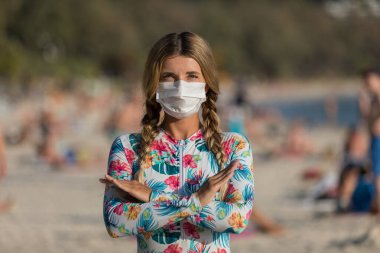 A woman and a child in a protective surgical mask on their face are standing on the beach in swimsuits. Chinese coronavirus disease COVID-19 is dangerous.