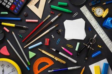 school supplies on black wood