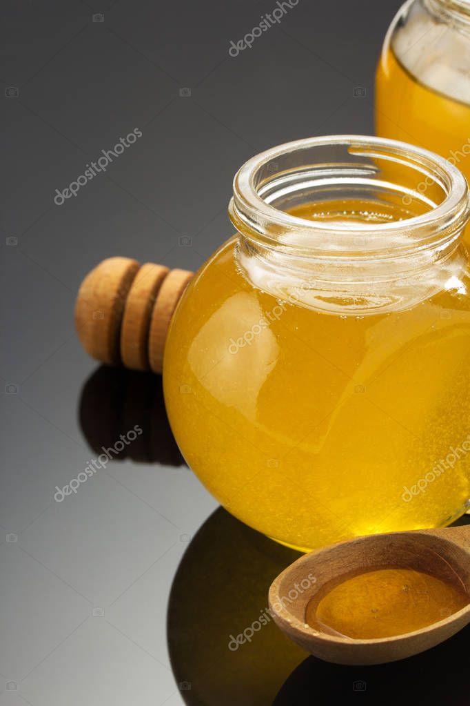 glass jar of honey on black