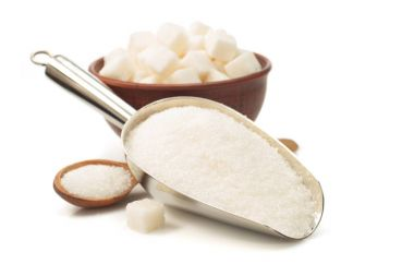 granulated sugar in scoop on white