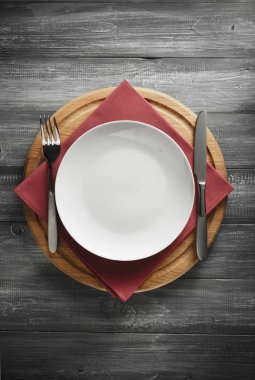 plate, knife and fork on rustic background