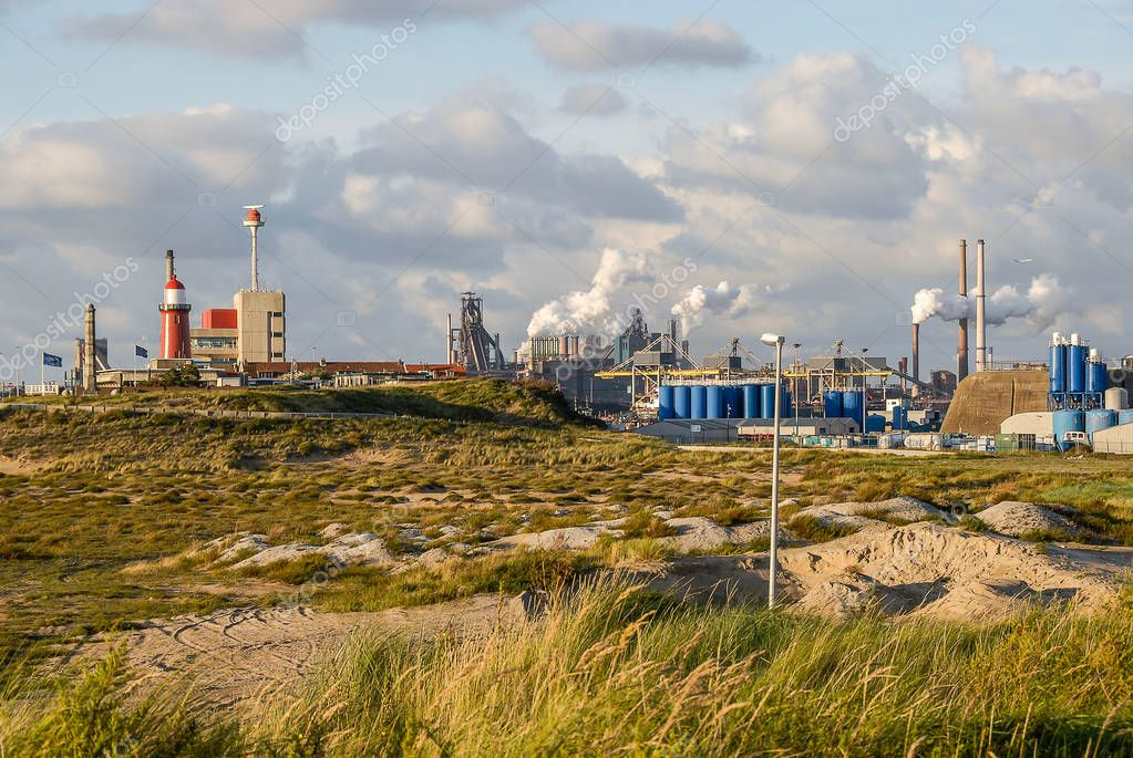 An industrial urban scenery of a steelworks with smoking pipes in IJmuiden, the Netherlands.