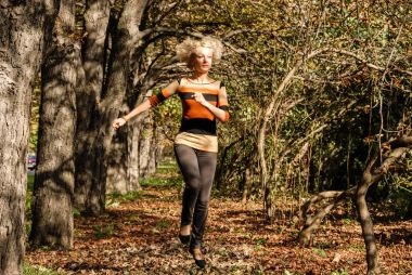 A young athletic blond hair woman runs jumping in a good mood in the park.