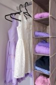 Photo Young girls clothes hanging in open wardrobe