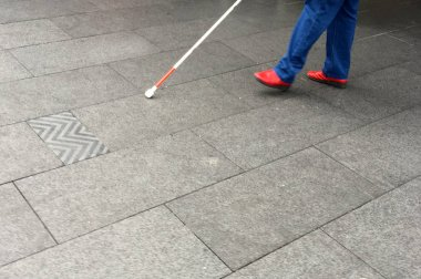 Visually impaired person walks in the street