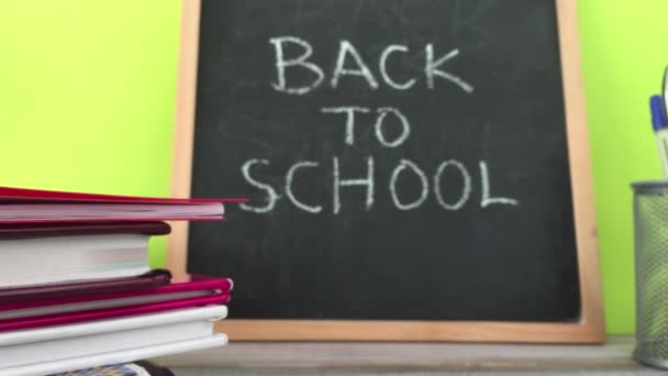 Back to school concept. Blackboard with text reading Back to School sign, pile of text books and stationary.