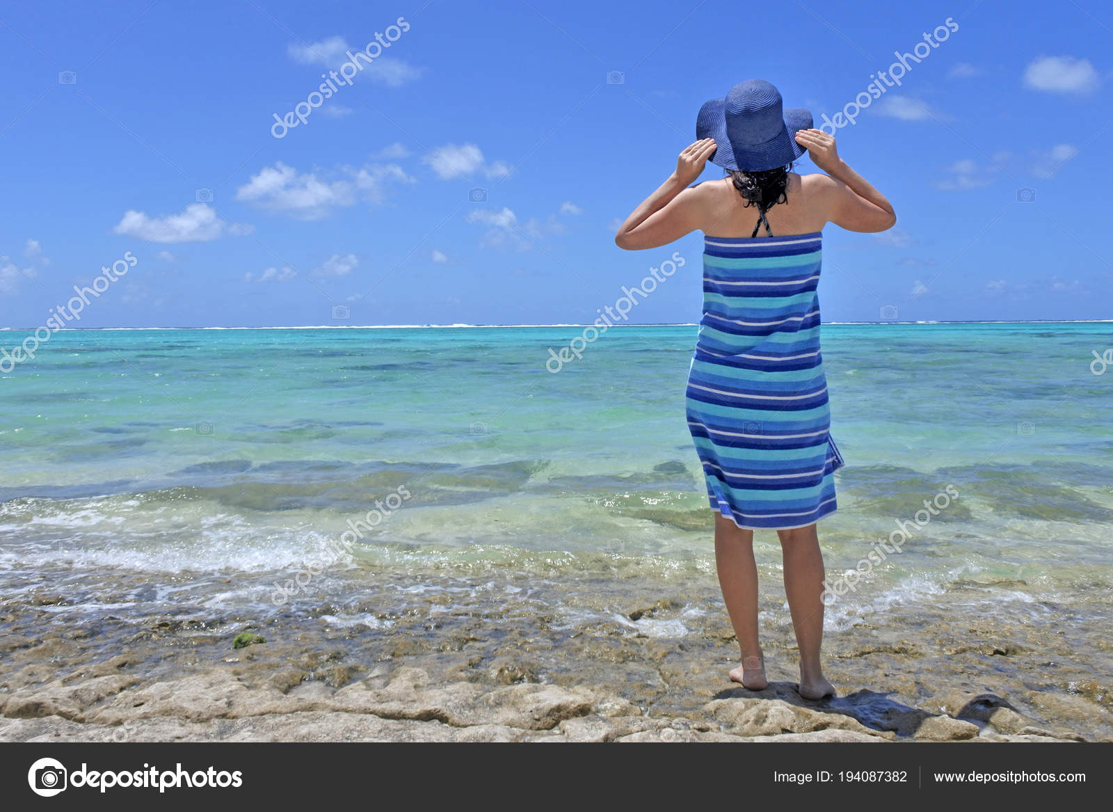 106a3a1db0e Woman wearing sun hat and wrapped in a beach towel stands on rocks and  looks at pacific island tropical resort lagoon in Rarotonga