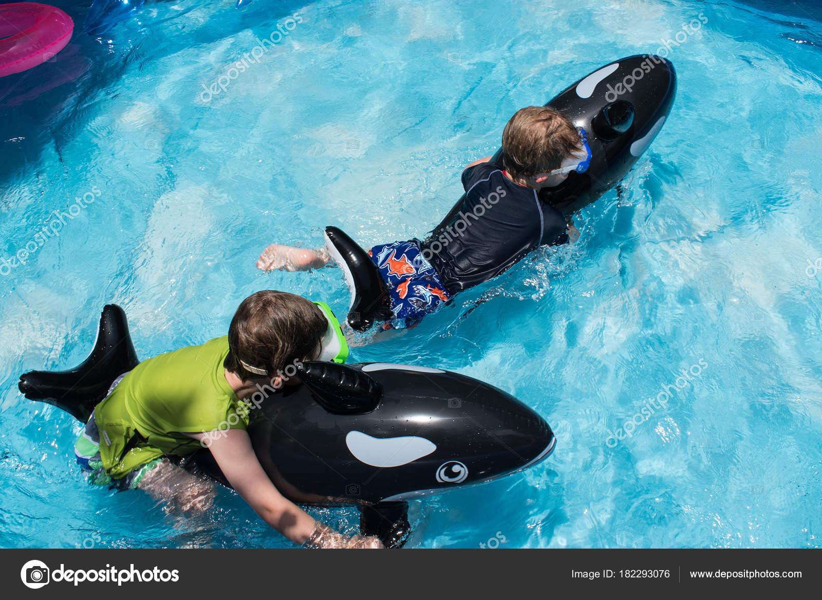 Zwei Jungen Schwimmer Hinterhof Pool Reiten Stockfoto
