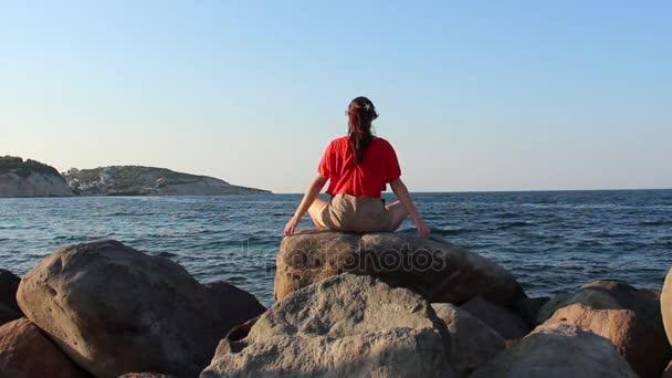 Žena, meditaci, jógu představují při západu slunce na pláži