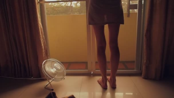 Young Barefoot Woman Looking At Rain Through The Glass Door Fan