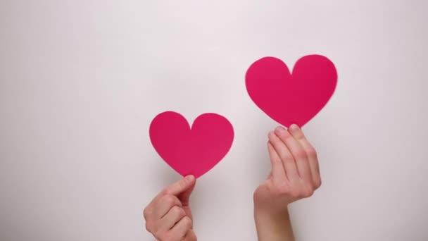 Detailní záběr ženských rukou držících srdce z červeného papíru skrz bílou papírovou stěnu. Valentines Day and Like blogging blog social network tender concept.