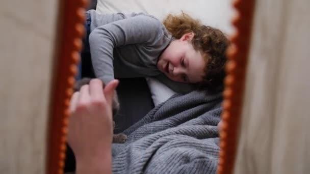 Boční pohled na nepoznatelný maminka a šťastný roztomilý malé dítě dcera hrát s kočkou ve stanu v dětském pokoji, užívat si a trávit čas spolu