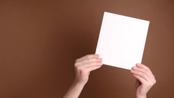 Az üres papírlapot tartó női kezek közelsége azt mutatja, hogy a barna háttér és a fénymásolási hely jóváhagyásra vagy megállapodásra került. Testbeszéd koncepció. Kézjel. Mint egy gesztus.