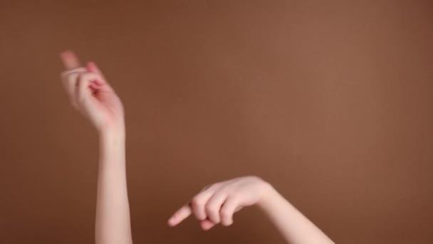 Unerkennbare weibliche Hände schnipsen ihre Finger zu Musik-Rhythmus-Geste isoliert über braunem Hintergrund im Studio. Kopierfläche für Werbung. mit Platz für Text oder Bild. Werbefläche, Attrappe.
