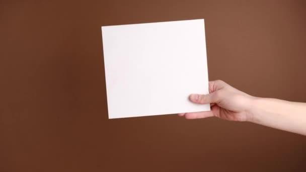 Nahaufnahme einer weiblichen Hand, die leeres weißes Papierblatt isoliert auf braunem Hintergrund mit Kopierraum hält. Körpersprache-Konzept.