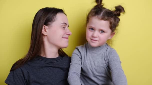 Šťastná veselá matka a dítě dívka mává rukama při pohledu na kameru, usmívající se maminka s dcerou dělat videohovory, rodina vloggers nahrávání videa spolu, sedí na pozadí žluté zdi