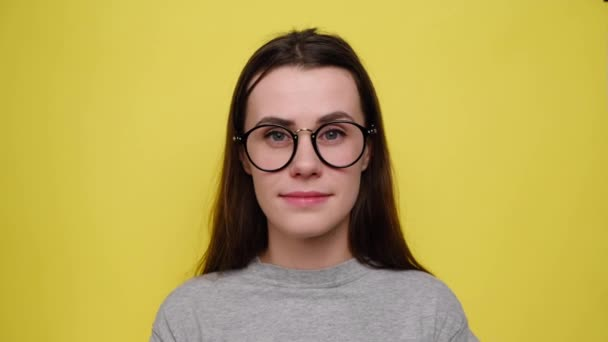 Closeup portrait woman reacts on unexpected surprise, spreads palms raised up, grins happily at camera, dressed in t-shirt and eyeglasses, isolated over yellow background