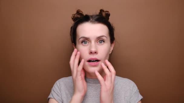 Verwirrte junge brünette Frau berührt Wange, öffnet Mund, hat Augen voller Angst und Enttäuschung, trägt graues T-Shirt, isoliert über braunem Hintergrund. Menschliche Mimik