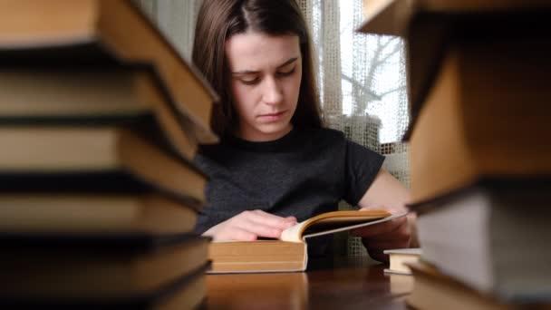 Közelkép nő diák ül az asztalnál készül teszt vizsga könyvek írása esszé tanfolyam jegyzetfüzetben tanul otthon. Lány egy halom könyvet tanul otthon vagy a könyvtárban