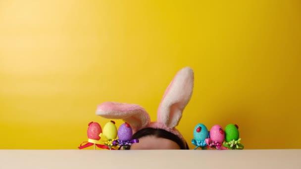Bájos vidám, vidám fiatal nő vadászni kezd a húsvéti tojásokra, bolyhos füleket visel, sárga háttér felett pózol fénymásoló hellyel. Szezonális nyaralás koncepció. Boldog húsvétot!!