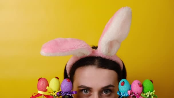 Frohe Ostern! Charmant fröhliche Frau beginnt, nach Ostereiern zu jagen, trägt flauschige Ohren, posiert vor gelbem Hintergrund mit Kopierraum. Saisonales Urlaubskonzept