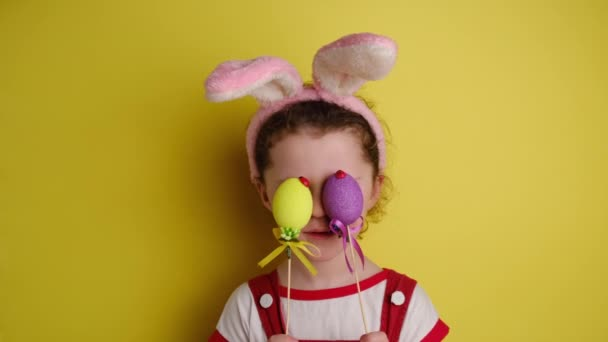 Glad cheerful little girl covers eyes with two Easter eggs, wears bunny ears, dressed in white t-shirt, models over yellow wall with free space for promotion. Spring holiday and Easter concept.