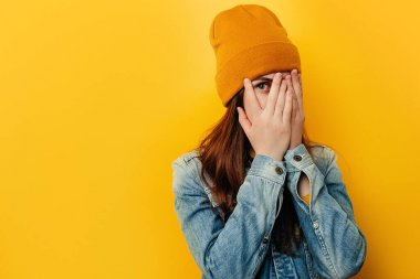 Shocked frightened young woman peeks through fingers, stares with widely opened eyes, wears denim jacket and hat, curious female student peek cover hide face in hands, isolated over yellow background