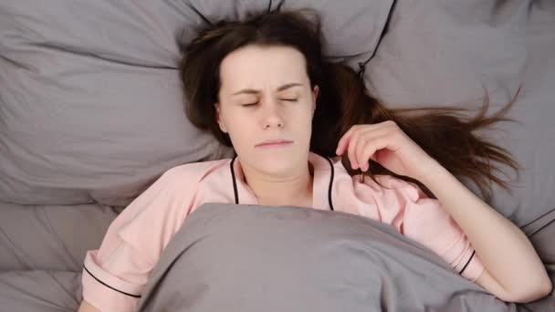 Horní pohled na nespokojenost mladé ženy má zachmuřenou tvář, má nespavost, nemůže spát pozdě, leží pod šedou přikrývkou, cítí se osamělá. Dáma byla vystresovaná, protože se příliš brzy probudila, trpěla nedostatkem spánku