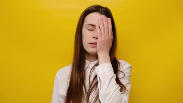 Trauriges ängstliches Mädchen, das sich Sorgen um seine Gesundheit macht, leidet an Migräne. Aufgebrachte besorgte Frau bedeckt Gesicht mit Handfläche, fühlt sich überlastet und müde, will schlafen, isoliert über gelbem Hintergrund