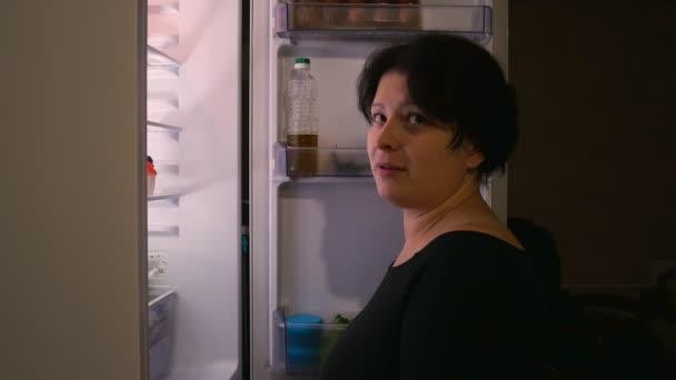 Žena stojí u ledničky a kolébky.Bere dort a usmívání.Bruneta.