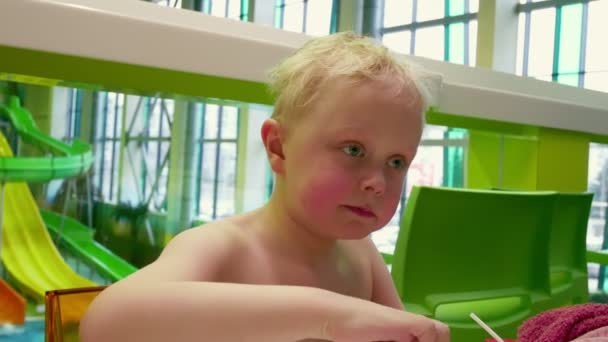 The kid eats French fries.A little boy with blond hair eats fast food.
