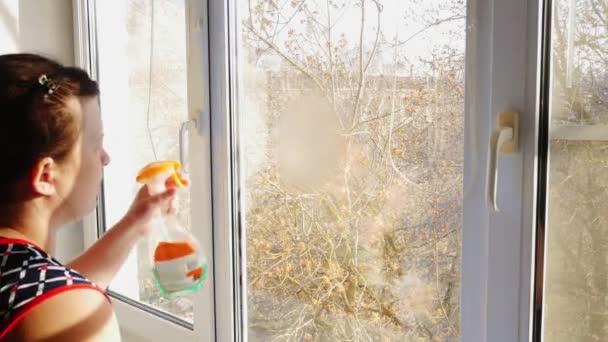 Frau im Bademantel wäscht Fenster in der Wohnung.