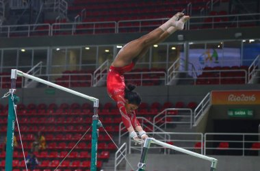 Olympic champion Gabby Douglas  of United States practices on the uneven bars before women's all-around gymnastics at Rio 2016 Olympic Games
