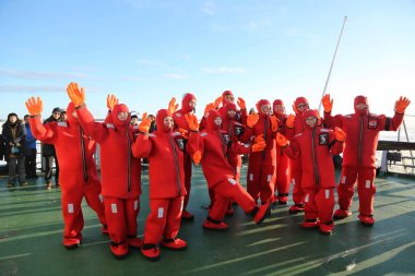 Unidentified tourists geared up with a survival suit ready to ice swim in frozen Baltic Sea.