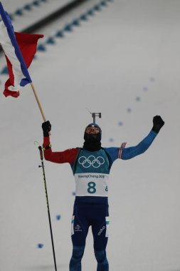 PYEONGCHANG, SOUTH KOREA - FEBRUARY 12, 2018: Olympic champion Martin Fourcade of France celebrates victory in biathlon men's 12.5km pursuit at the 2018 Winter Olympics in Alpensia Biathlon Centre