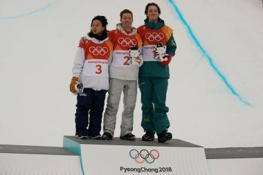 PYEONGCHANG, SOUTH KOREA  - FEBRUARY 14, 2018: Ayumu Hirano JPN (L),  Shaun White USA and Scotty James AUS during venue ceremony after men's snowboard halfpipe final at the 2018 Winter Olympics