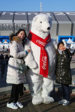 GANGNEUNG, SOUTH KOREA - FEBRUARY 17, 2018: Sport fans take picture with Coca Cola Bear in Gangneung Olympic Park during 2018 Winter Olympic Games. Coca-Cola has been a sponsor of the games since 1928