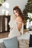 Porträt eines Model-Mädchens mit hellem Make-up umarmt dicke wütende Katze mit festlicher Weihnachtsbeleuchtung auf dem Hintergrund. schöne junge Frau mit hellem Make-up in warmem Pullover mit britischer Katze